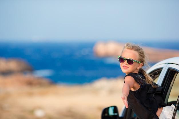 Urocza mała dziewczynka na wakacyjnej podróży samochodem z pięknym krajobrazem Premium Zdjęcia