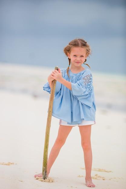 Urocza mała dziewczynka podczas wakacji na plaży ma zabawę Premium Zdjęcia