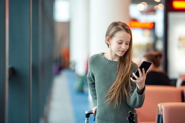 Urocza Mała Dziewczynka Przy Lotniskiem W Dużym Lotnisku Międzynarodowym Blisko Okno Premium Zdjęcia