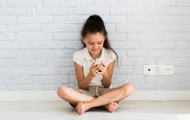 Urocza mała dziewczynka używa jej smartphone Darmowe Zdjęcia