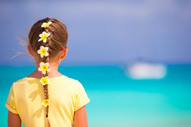 Urocza Mała Dziewczynka Z Frangipani Kwitnie W Włosy Na Plaży Premium Zdjęcia