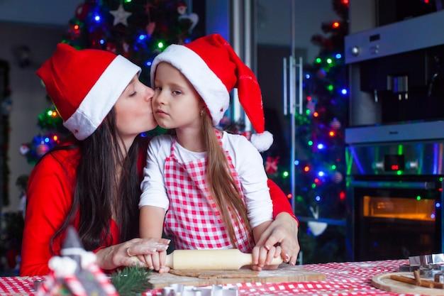 Urocza mała dziewczynka z matką jest ubranym santa kapelusze piec wpólnie bożenarodzeniowych piernikowych ciastka Premium Zdjęcia