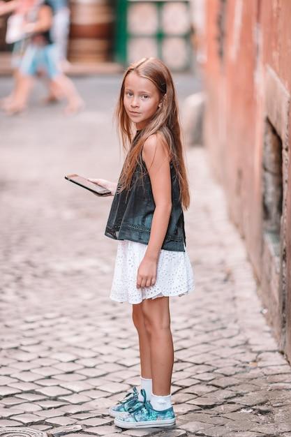 Urocza mała dziewczynka z telefonem komórkowym przy włoskim miastem podczas wakacje Premium Zdjęcia