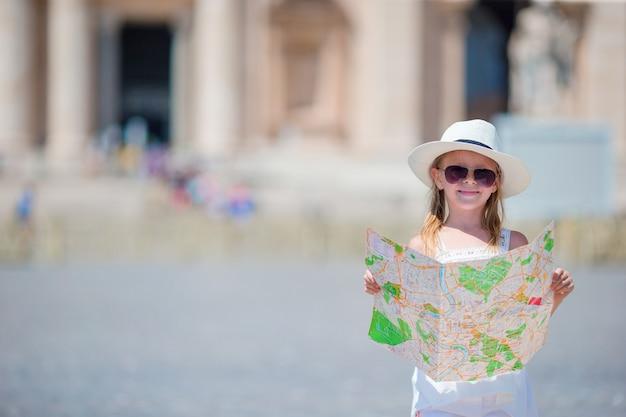 Urocza mała dziewczynka z turystyczną mapą Premium Zdjęcia
