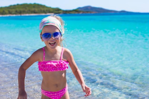 Urocza mała dziewczynka zabawy w płytkiej wodzie na tropikalnej plaży Premium Zdjęcia