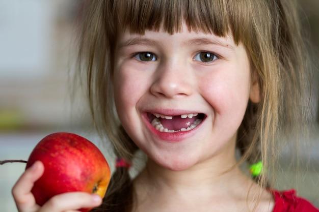 Urocza, Mała, Kręcona Bezzębna Dziewczyna Uśmiecha Się I Trzyma Czerwone Jabłko. Portret Szczęśliwy Dziecko Je Czerwonego Jabłka. Dziecko Traci Zęby Mleczne. Zdrowe Odżywianie. Premium Zdjęcia