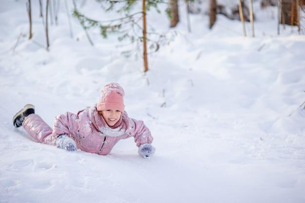 Urocza mała szczęśliwa dziewczyna na sankach w zima śnieżnym dniu. Premium Zdjęcia