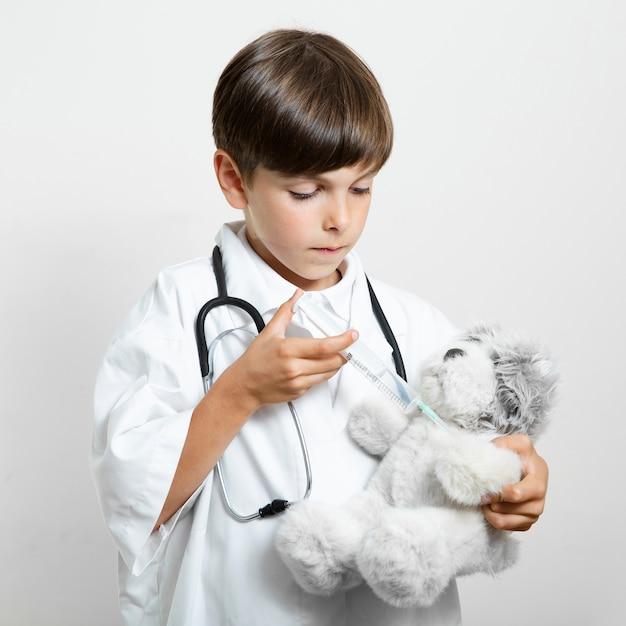 Urocza młoda chłopiec trzyma misia Darmowe Zdjęcia