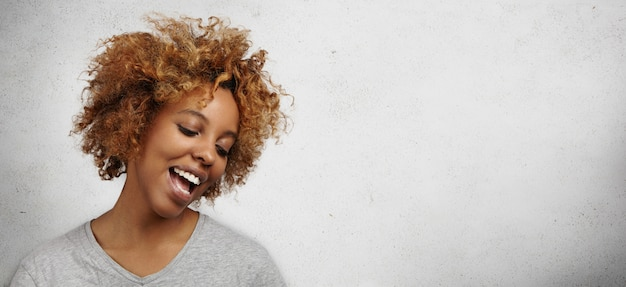 Urocza Młoda Ciemnoskóra Kobieta Ze Stylową Fryzurą I Piercingiem Na Twarzy, Szeroko Otwierająca Usta, Spoglądająca W Dół Z Radosnym I Szczęśliwym Uśmiechem. Darmowe Zdjęcia