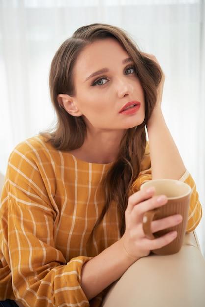 Urocza młoda kaukaska kobieta pozuje w domu na leżance z filiżanką kawy Darmowe Zdjęcia