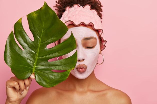 Urocza Młoda Kobieta Afro Nakłada Odżywczą Maseczkę Z Glinki, Ma Zamknięte Oczy, Usta Złożone, Zakrywa Połowę Twarzy Dużym Zielonym Liściem, Nosi Opaskę Prysznicową, Odizolowaną Na Różowej ścianie Darmowe Zdjęcia
