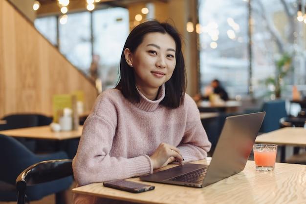 Urocza Młoda Kobieta O Azjatyckim Wyglądzie Pracuje Na Laptopie W Kawiarni. Koncepcja Pracy Poza Domem, Na Zlecenie. Premium Zdjęcia