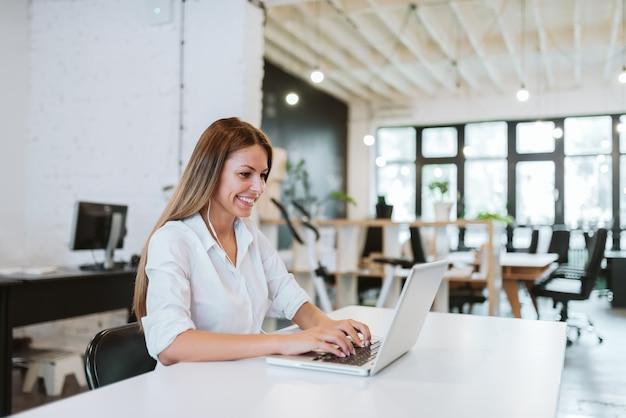 Urocza młoda kobieta pracuje w nowoczesnym biurze współpracy. Premium Zdjęcia
