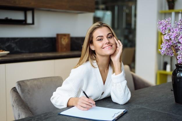 Urocza Młoda Kobieta Siedzi Przy Stole W Kuchni I Pisze W Zeszycie. Tworzenie Listy Zakupów Do Domu. Premium Zdjęcia