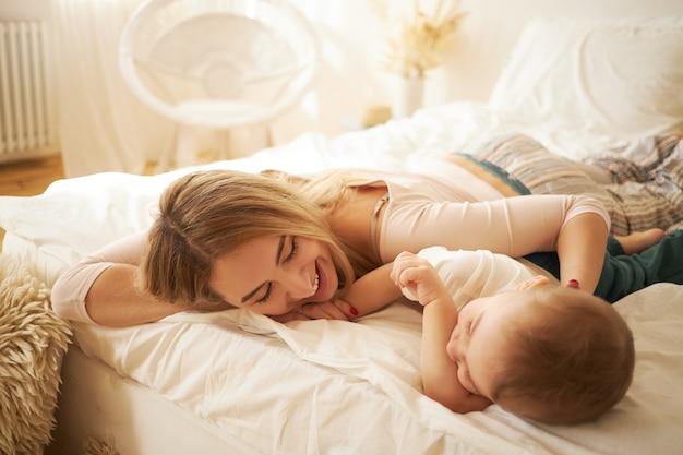 Urocza Młoda Mama W Nocnym Kostiumie Wylegująca Się W łóżku Ze Swoim Słodkim Dzieckiem, Rozmawiająca Ze Sobą Po Przebudzeniu, Z Radosnym Wyrazem Twarzy. Rodzina Bonnds, Macierzyństwo I Koncepcja Niemowlęctwa Darmowe Zdjęcia