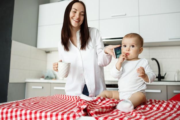 Urocza Młoda Matka Daje Telefon Dziecku I Uśmiechnięta Darmowe Zdjęcia