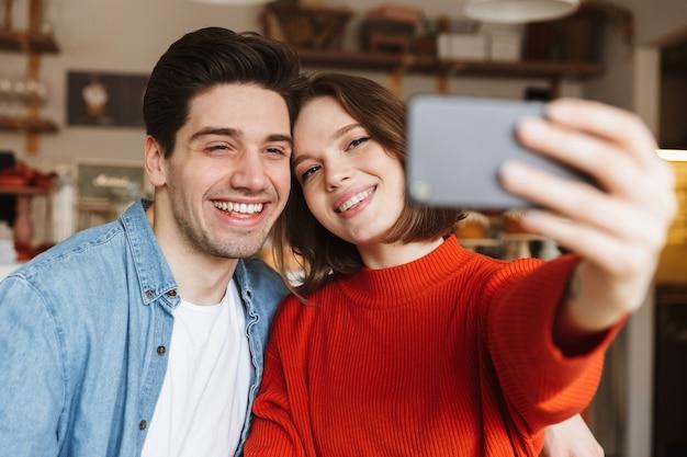Urocza Młoda Para Siedzi Przy Stoliku W Kawiarni Premium Zdjęcia
