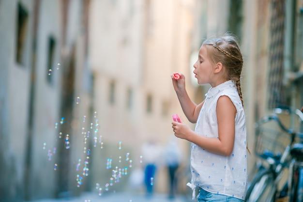 Urocza mody mała dziewczynka na zewnątrz w europejskim mieście rzym Premium Zdjęcia