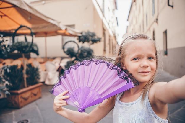 Urocza mody mała dziewczynka outdoors w europejskim mieście Premium Zdjęcia