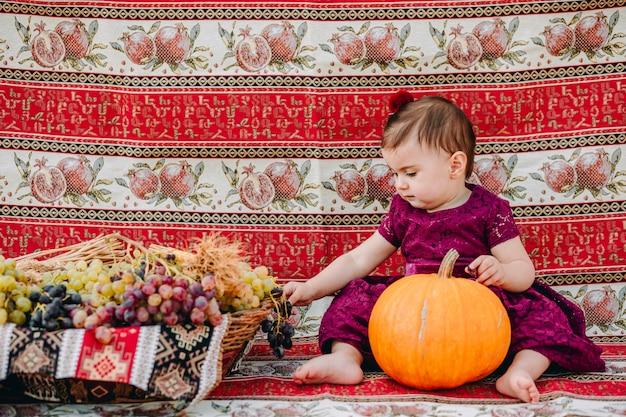 Urocza Ormiańska Dziewczynka Trzyma Dyni I Zbiera Winogrona W Słomianym Koszu Premium Zdjęcia