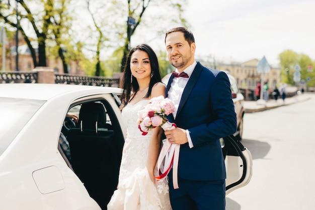 Urocza para małżeńska stoi obok siebie w pobliżu samochodu Premium Zdjęcia