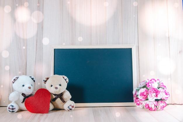 Urocza para niedźwiedź siedzi blisko blackboard i słodkich róż na podłoga, valentine pojęcie Premium Zdjęcia