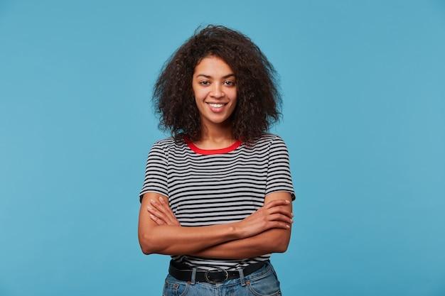 Urocza Pewna Siebie Szczęśliwa Młoda Kobieta O Figlarnym Wyglądzie Ma Fryzurę Afro śmiejącą Się, Uśmiechając Się Do Niebieskiej ściany Darmowe Zdjęcia