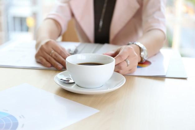 Urocza Piękna Opalona Skóra Azjatycka Elegancka Inteligentna Kobieta Ręcznie Pracuje Na Telefonie Komórkowym I Pisze Długopis Na Mleczarni Notebooka Na Drewnianym Stole W Biurze. Zaprezentuj Swój Produkt Kobiecie, Wykonując Dobrą Pracę. Premium Zdjęcia