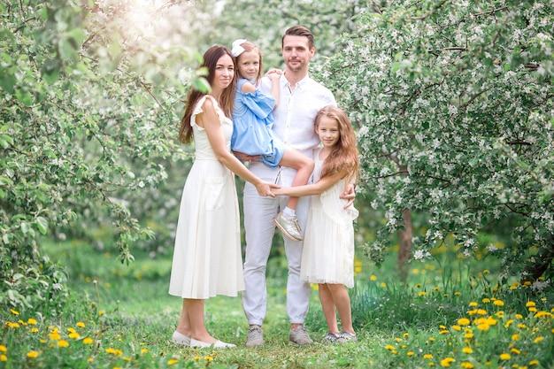 Urocza rodzina w kwitnącym wiśniowym ogrodzie w piękny wiosenny dzień Premium Zdjęcia