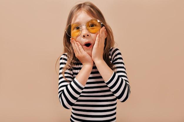 Urocza śliczna Mała 6-letnia Dziewczynka Z Jasnymi Włosami W Koszuli W Paski Pozuje Z Otwartymi Ustami I Trzyma Ręce Na Czeku Darmowe Zdjęcia