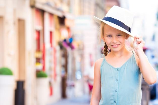 Urocza szczęśliwa mała dziewczynka outdoors w europejskim mieście. Premium Zdjęcia