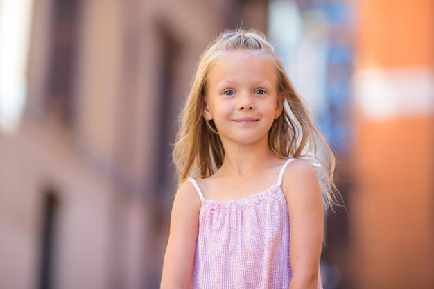 Urocza szczęśliwa mała dziewczynka outdoors w włoskim mieście. portret caucasian dzieciak cieszy się wakacje w rzym Premium Zdjęcia