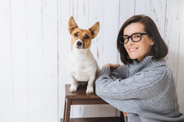 Urocza Zadowolona Zadowolona Kobieta Nosi Okulary I Luźny Ciepły Sweter Premium Zdjęcia
