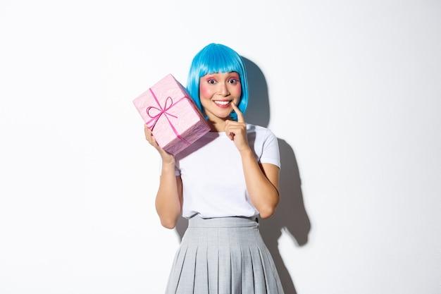 Urocza Zaintrygowana Azjatka Próbuje Odgadnąć, Co Znajduje Się W Pudełku Prezentowym, Odbiera Prezent Na Wakacje Lub Urodziny, Stoi. Premium Zdjęcia