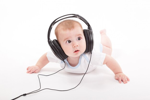 Urocze Dziecko Na Białym Tle Ze Słuchawkami Do Słuchania Premium Zdjęcia