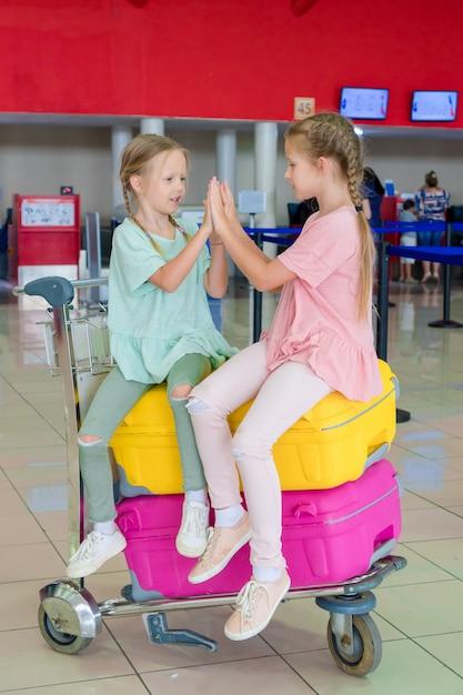 Urocze dziewczynki bawiące się na lotnisku czekające na wejście na pokład Premium Zdjęcia