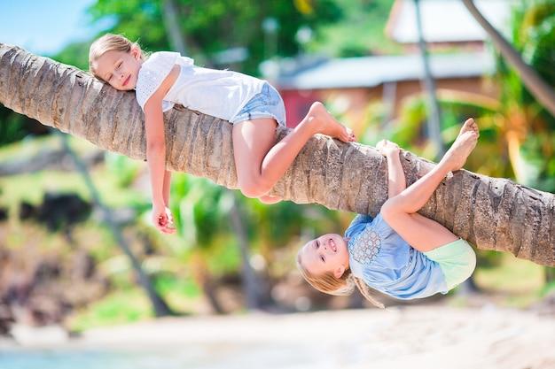 Urocze Dziewczynki Na Tropikalnej Plaży Zabawy Na Palmie Podczas Letnich Wakacji. Dzieci Lubią Wakacje Jak Małpy Premium Zdjęcia