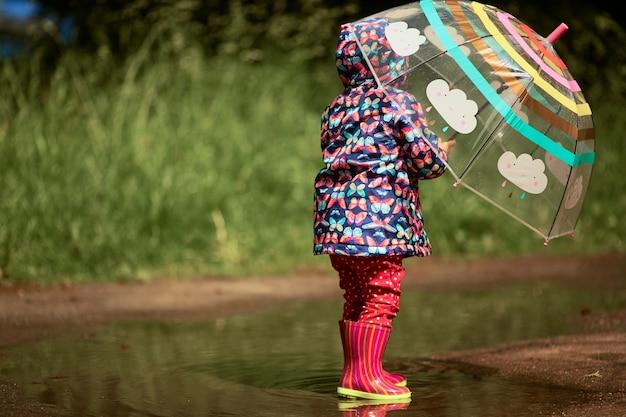Urocze Dziewczynki Z Parasolem Ma Zabawy Stojące W Gumboots W Basenie Po Deszczu Darmowe Zdjęcia