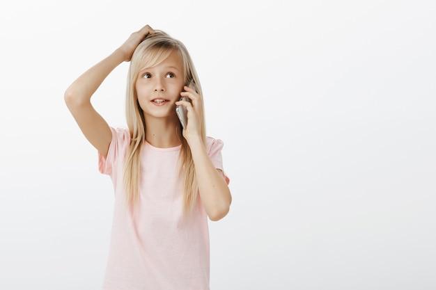 Urocze Inteligentne Dziecko Kobiece O Blond Włosach, Rozmawiające Na Smartfonie, Drapiące Się Po Głowie I Odwracające Wzrok Darmowe Zdjęcia