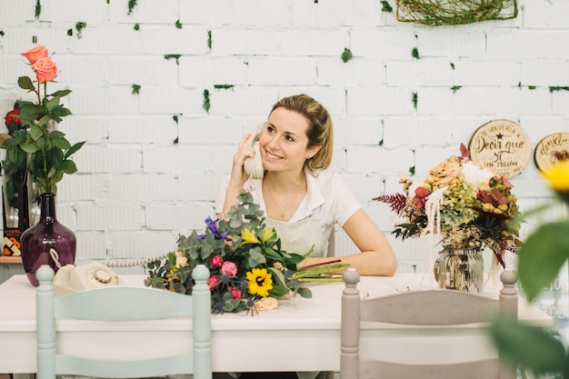 Urocze Kwiaciarnia Rozmawia Przez Telefon Przy Stole Darmowe Zdjęcia