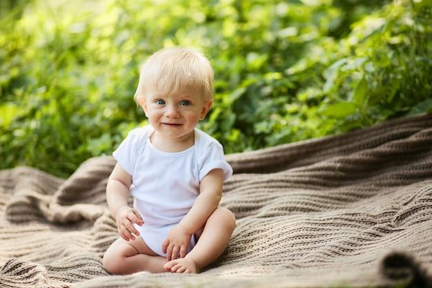 Urocze małe blond chłopiec ma zabawy siedzi na pled w parku latem Darmowe Zdjęcia