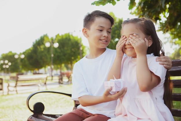 Urocze Małe Dzieci Korzystających Z Ciepłego Słonecznego Dnia W Parku Premium Zdjęcia
