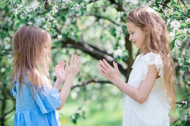 Urocze małe dziewczynki w kwitnącym jabłoń ogródzie na wiosna dniu Premium Zdjęcia