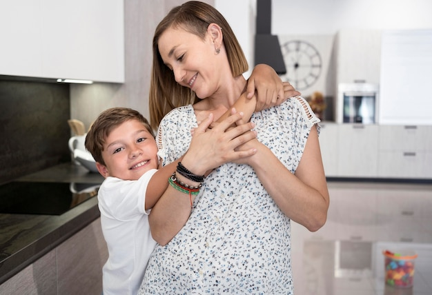 Uroczy Chłopiec Przytula Swoją Matkę W Domu Darmowe Zdjęcia