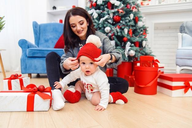 Uroczy Maluch Z Matką Rozpakowujący świąteczny Prezent. Premium Zdjęcia