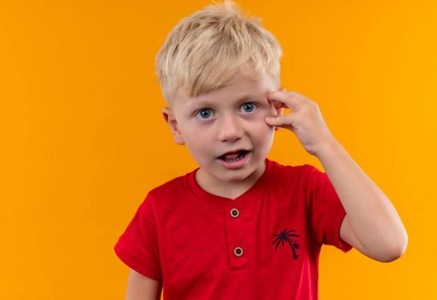 Uroczy Mały Chłopiec O Blond Włosach I Niebieskich Oczach Ubrany W Czerwoną Koszulkę Zaskakuje I Trzyma Rękę Na Głowie Darmowe Zdjęcia