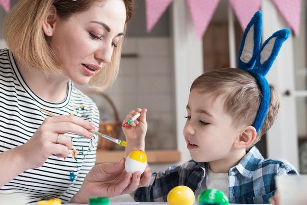 Uroczy Mały Chłopiec Uczy Się Malować Jajka Na Wielkanoc Darmowe Zdjęcia