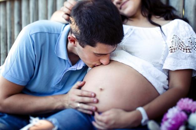 Uroczy mężczyzna całuje delikatny ciężarny brzuch swojej damy w białej koszuli Darmowe Zdjęcia