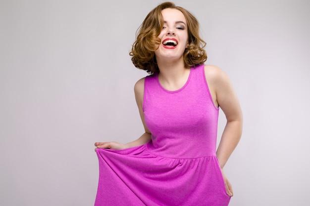 Uroczy młoda dziewczyna w różowej sukience na szarym tle. młoda dziewczyna wyciąga rękę Premium Zdjęcia