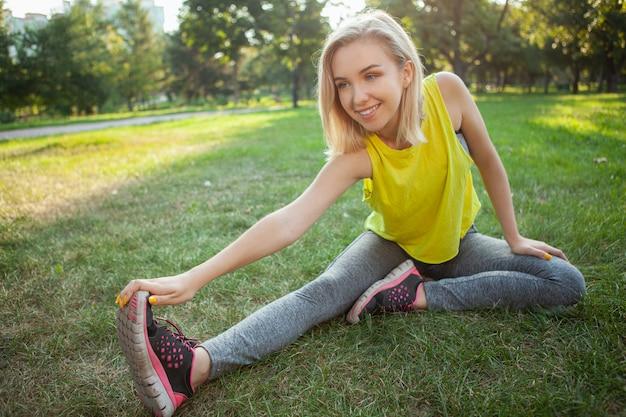Uroczy młoda sportsmenka ćwiczenia w parku w godzinach porannych Premium Zdjęcia